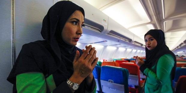 Rayani Air flight attendants pray before departure at Kuala Lumpur International Airport. Photo / AP