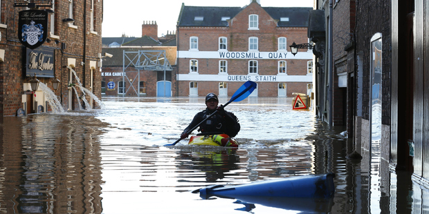 A man paddles along flooded streets in York city centre. Photo / Getty