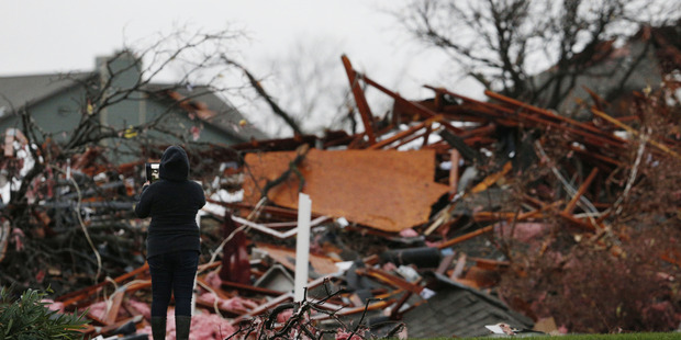 Residents take a picture near a pile of debris at an apartment complex damaged by the tornadoes. Photo: Nathan Hunsinger/The Dallas Morning News via AP