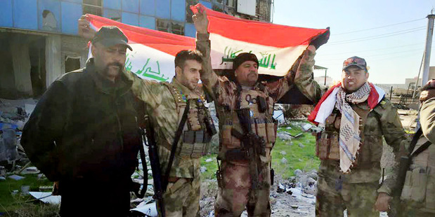 Iraqi soldiers hold national flags in the government complex in central Ramadi. Photo / AP
