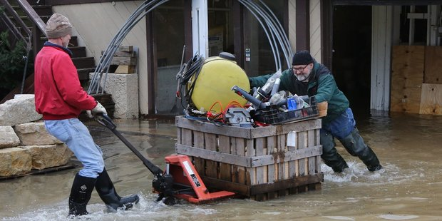 People move items to higher ground at the Fenton Feed Mill. Photo / AP
