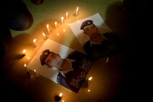 Members of Al-Kaseasbeh, the tribe of Jordanian pilot, Lt. Muath al-Kaseasbeh, captured by Isis, light candles by posters with his picture. Photo / AP