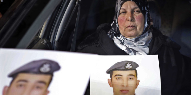 Jan. 27, 2015 file photo, the mother of Jordanian pilot Lt. Mu'ath al-Kaseasbeh holds a picture of her son. Photo / AP
