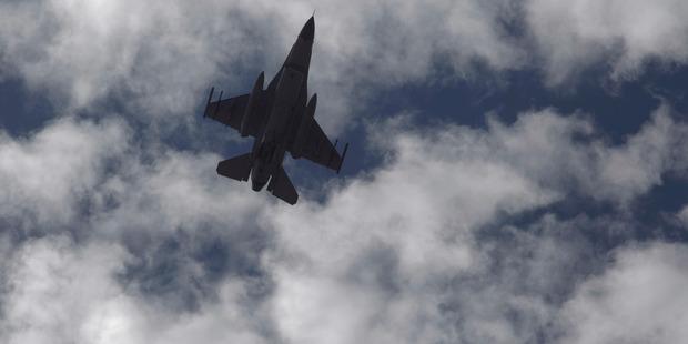 A Jordanian Air Force fighter jet flies over the village of Ai as Jordanian King Abdullah II visits to offer his condolences to the tribe of the slain Jordanian pilot. Photo / AP