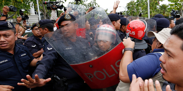 Malaysian police officers struggle with supporters of Malaysian opposition leader Anwar Ibrahim outside Malaysia's top court yesterday. Photo / AP