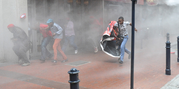 Protesters flee water canon fire near parliament in Cape Town ahead of the State Of The Nation Address by South African president Jacob Zuma. Photo / AP