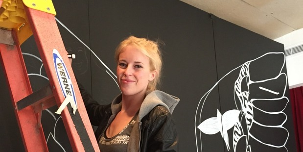 Kelsey Montague in action painting one of her angel wing murals. Photo: http://kelseymontagueart.com/