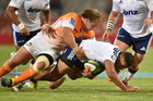 Charles Piutau of the Blues getting tagged by Torsten van Jaarsveld of the Cheetahs. Photo / Getty Images