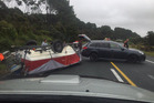 A boat lies upturned on State Highway 1 south of Whangarei. Photo / Supplied