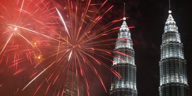 Fireworks explode in front of Malaysia's landmark building, Petronas Twin Towers, during the New Year's Eve celebration in Kuala Lumpur. Photo / AP