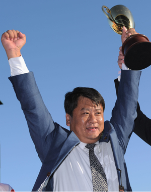 Winning owner Lang Lin poses with trophy after racehorse Mongolian Khan wins Race 9 at the Melbourne Cup. Photo / NZ Herald