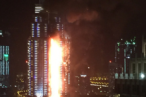 Smoke and flames pour from the Address Downtown hotel tower shortly before the New Year's fireworks display. Photo / Getty Images