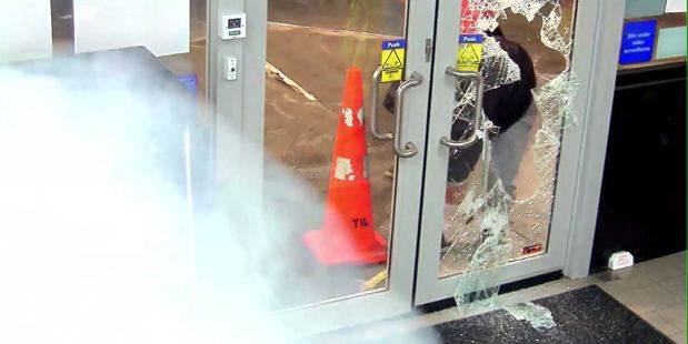Mobil petrol station CCTV cameras show the offenders smashing their way into the store before the fog is released. Photo / Supplied