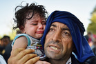 A Syrian migrant and his child try to board a train in Croatia. File Photo / Getty Images
