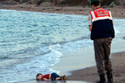 A paramilitary police officer investigates the scene before carrying the lifeless body of 3-year-old Alan Shenu from a Turkish beach. PHOTO/FILE