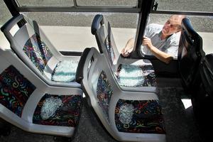 Nimon buses general manager Pete Patterson checks the broken windows of the vandalised bus. Photo / Warren Buckland