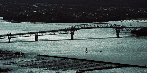 A yacht sails next to the Auckland harbour bridge. Photo / Getty Images