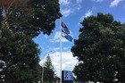 The current flag and Kyle Lockwood's silver fern design flying at Auckland Airport.