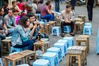 Huddled on small plastic chairs, locals and visitors drink bia ho.