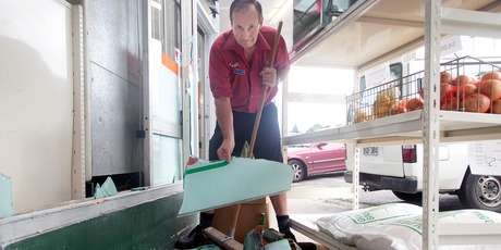 Store owner Gary Henwood cleans up the mess after a burglary. Photo/Andrew Warner