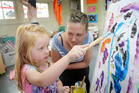 WORK OF ART: Sam Belk, 3, painting with Christine Ferguson who was helping out at the Springvale Playcentre.