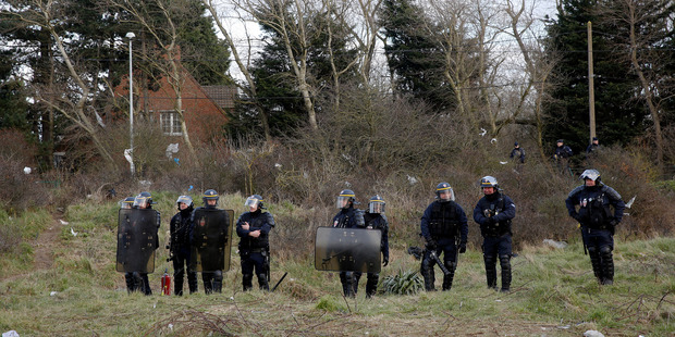 French riot police stand on a perimeter of a makeshift camp near Calais. Photo / AP