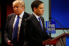 Republican presidential candidate, businessman Donald Trump passes behind Sen. Marco Rubio, R-Fla., during a commercial break at Republican presidential primary debate. Photo / AP