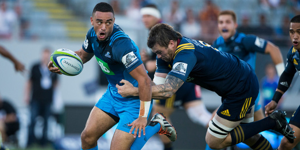Blues halfback Bryn Hall bursts away from Highlanders no.8 Liam Squire in the opening match of Super Rugby season between the Blues and the Highlanders at Eden Park.