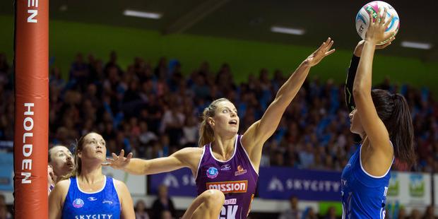 Northern Mystics Maria Tutaia on the attack against Queensland Firebirds player Laura Geitz. Photo / Nick Reed