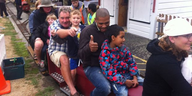 """Newly arrived refugees and Wairarapa Anglican parishioners enjoy a ride on the Mini Train in Featherston last year for """"A Day in the Country"""". PHOTO/SUPPLIED"""