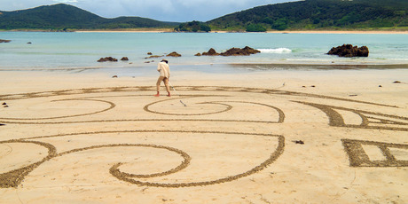 INTER-TIDAL ART: Earthscape artist Andrea Amador at work at Maitai Bay on Monday evening, right.