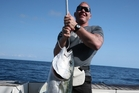 Shane Cameron is happy with his first kingfish. Picture / Geoff Thomas