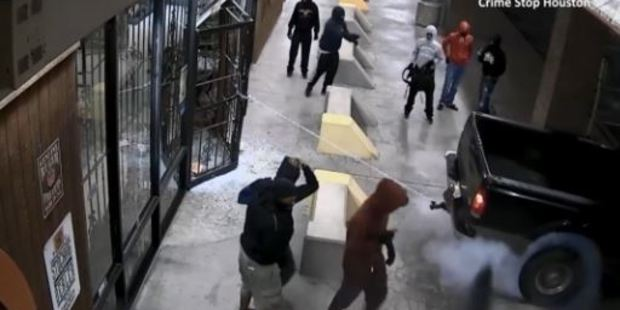 Loading The footage shows several people tying chains to a black Ford F-250 and the door of the store, before revving to yank it off its hinges. Photo / Crime Stop Houston