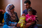 Baby Rima and her sister with her mother, Kholoud Suliman, and father, Mohammed Salameh, in their home at the Zaatari refugee camp in Jordan. Photo / Lorenzo Tugnoli, The Washington Post