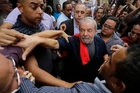 Brazil's former President Luiz Inacio Lula da Silva is surrounded by supporters as he leaves the Workers' Party building in Sao Paulo. Picture / AP
