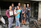 From left: Herani Clair, 11, holding a family photo album that survived the blaze, Waipawa fire brigade senior firefighter Alison Ludlow, Rhythm Houkamau, 4, Lisa Clair, Waipawa fire brigade chief fire officer Brian Edwards, Ariarnah Houkamau, 3, Thomas Houkamau and Waipawa senior station officer Gwyn Burton at the Shanley St house that was gutted by fire recently. Photo / Nicki Harper