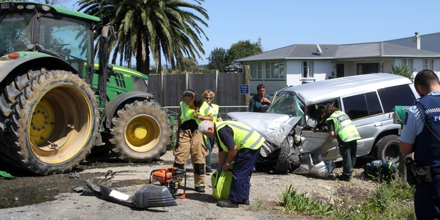 RESCUE BEGINS: Kaitaia firefighters setting up the jaws of life to release the passenger from the car that collided with a tractor (left) on the Awanui Straight yesterday.
