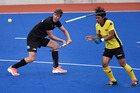 A Malaysian defender loses his stick as Black Sticks striker James Coughlan attacks at Blake Park yesterday. Photo / George Novak