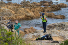 Police and ambulance officers on the foreshore where they recovered the body of a 37-year-old diver at Island Bay in Wellington. Photo / Mark Mitchell