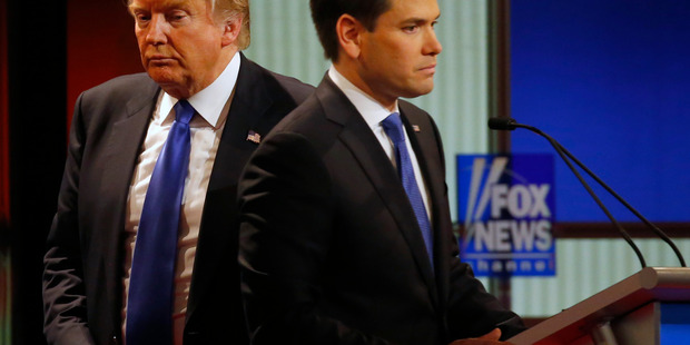 Republican presidential candidate, businessman Donald Trump passes behind Sen. Marco Rubio, R-Fla., during a commercial break at Republican presidential primary debate at Fox Theatre, Thursday, March