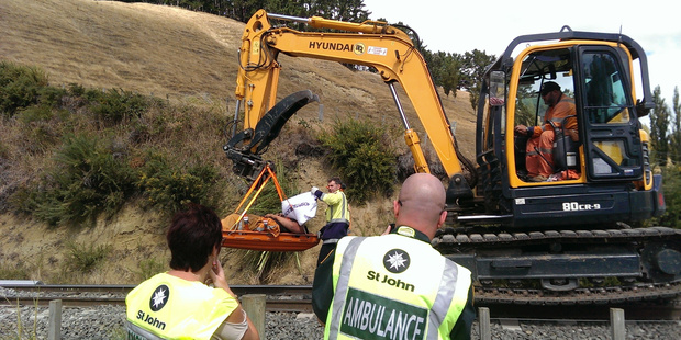 KIWI INGENUITY: Rescuers had the bright idea to suspend the injured man's stretcher from a digger and drive it to the ambulance, which couldn't reach them.