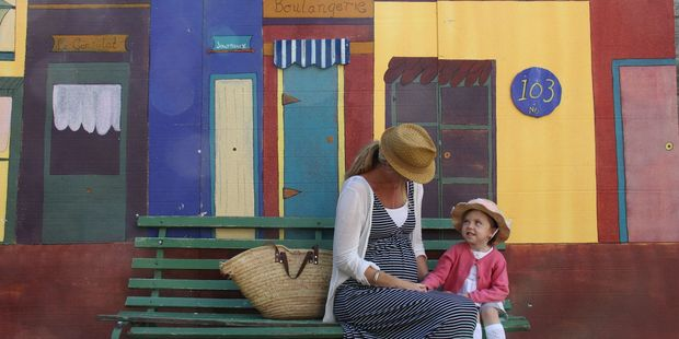 QUIET: Lynore Daniels, of Waikanae, with Lacey, 4, alongside the French mock-up of terrace housing, built along a racecourse building wall.PHOTO/ANDREW BONALLACK