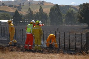 Fire crews at the aftermath of a fire at a Wilton Rd farming property in rural Carterton. PHOTO/EMILY NORMAN