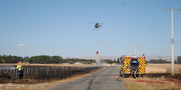 Helicopters dump water from monsoon buckets to help douse a blaze at a Carterton farm on Sunday. PHOTO/EMILY NORMAN