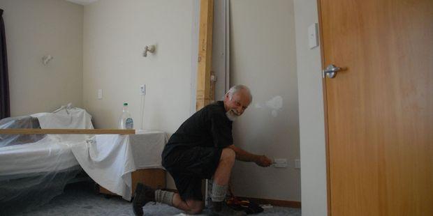 Electrician John Hudson hard at work helping upgrade a room at Carter Court. PHOTO/ALISA YONG