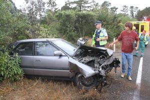 The driver of the Mazda sedan walks around the car while Masterton police traffic sergeant Chris Megaw photographs the damage. PHOTO/ANDREW BONALLACK