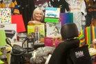 McDowell Real Estate rentals manager Carol de Farias surrounded by the items up for grabs at the charity event tomorrow.