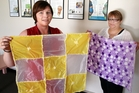 Angela Adam (left) holds a stitched blanket made out of plastic supermarket bags. Lucy Pettit holds a polar fleece blanket. They say wrapping your baby in either has the same effect: Overheating. Photo / Stuart Munro