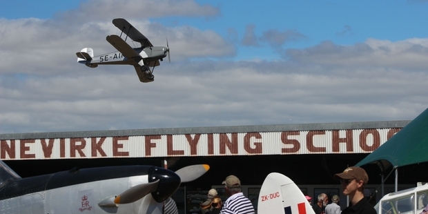 A vintage plane swoops low over the Dannevirke Flying School hangar, where artist Mike Harold had his Topdressing Daze exhibition last Saturday. Left, is the plane HRH Prince Phillip learnt to fly in.