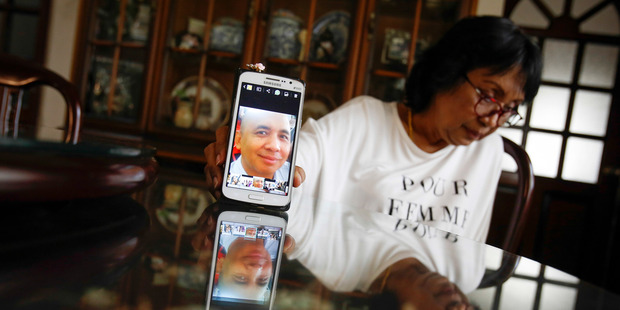 Sakinab Shah, sister of Captain Zaharie Ahmad Shah, holds up her mobile phone with her last photo of her brother. Photo / AP